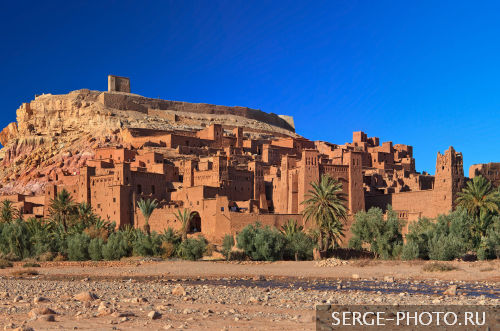 Aït Benhaddou  Aït Benhaddou is a 'fortified city', or ksar, along the former caravan route between the Sahara and Marrakech in present-day Morocco.